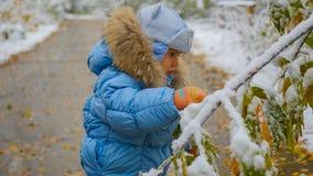 愉快的儿童游戏在有多雪的树的一个公园 免版税库存照片
