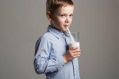 愉快的儿童饮用奶 小微笑的男孩享用牛奶鸡尾酒 免版税库存照片