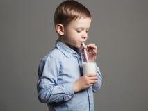 愉快的儿童饮用奶 小微笑的男孩享用牛奶鸡尾酒 免版税库存图片