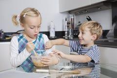 愉快的兄弟和姐妹混合的面团一起在厨房里 免版税库存照片