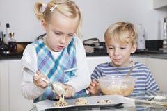 愉快的兄弟和姐妹烘烤曲奇饼在厨房里 免版税库存图片
