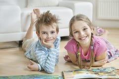 愉快的兄弟姐妹画象有故事的在客厅预定说谎在地板上 库存照片