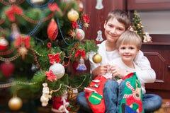愉快的兄弟 婴孩圣诞节克劳斯帽子演奏s圣诞老人的母亲照片一起佩带 免版税库存图片