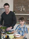 愉快的准备沙拉的父亲和儿子在厨台 库存照片