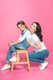 愉快的凳子的微笑在桃红色的母亲和逗人喜爱的矮小的女儿 库存图片