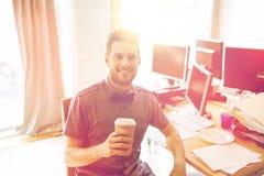 愉快的创造性的男性办公室工作者饮用的咖啡 免版税库存照片