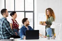 愉快的创造性的队用运作在办公室的咖啡 免版税库存图片