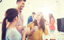 愉快的创造性的队饮用的咖啡在办公室 库存图片