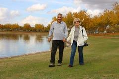 愉快的前辈走在公园的退休的夫妇 免版税库存照片