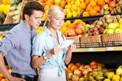 愉快的加上反对果子堆的购物单  免版税库存图片