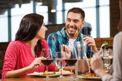 愉快的加上吃在餐馆的朋友 免版税库存照片