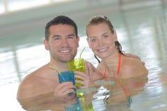 愉快的加上在游泳池的两块玻璃 免版税库存照片