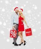 愉快的加上在雪的红色购物袋 免版税库存图片