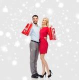 愉快的加上在雪的红色购物袋 图库摄影