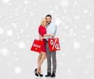 愉快的加上在雪的红色购物袋 库存照片