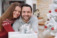 年轻愉快的加上坐在firepla附近的圣诞节的礼物 免版税库存照片