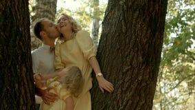 愉快的加上她的亲吻在森林背景的小女儿 图库摄影