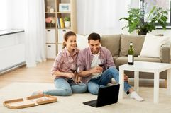 愉快的加上膝上型计算机饮用的红酒在家 免版税库存照片