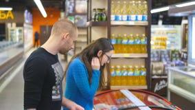 年轻愉快的加上过来对冷冻机在杂货店和采摘与冻的购物车包裹 股票视频