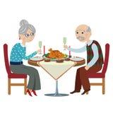 愉快的动画片祖父母在一张欢乐桌上 库存图片
