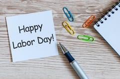 愉快的劳动节-在木桌背景的消息与办公用品 劳动节庆祝在5月1日 春天…上升了叶子,自然本底 免版税库存照片