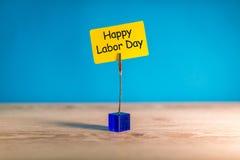 愉快的劳动节-在被别住的黄色笔记的消息在蓝色背景 劳动节庆祝在5月1日 春天…上升了叶子,自然本底 库存照片