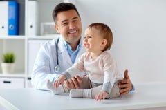 愉快的医生或儿科医生有婴孩的诊所的 图库摄影
