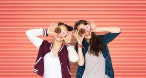 愉快的十几岁的女孩或朋友有油炸圈饼的在眼睛 库存图片