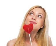 愉快的十几岁的女孩画象有心形的lollypop的 免版税库存照片