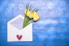 愉快的华伦泰或母亲节背景 黄色郁金香美丽的花束在一个开放信封的与说谎在a的心脏标志 图库摄影