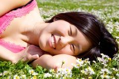 愉快的华裔美国人女孩微笑的和放松的放置在与花的草 免版税图库摄影