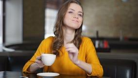 愉快的单独妇女饮用的热奶咖啡,要求侍者票据,放松 股票录像