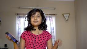愉快的印度亚裔享受在流动点头的听的音乐,跳舞和唱歌曲画象的白种人女孩佩带的耳机 影视素材