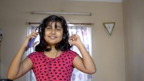 愉快的印度亚裔享受在流动点头的听的音乐,跳舞和唱歌曲画象的白种人女孩佩带的耳机 股票录像