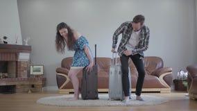 愉快的卷曲女孩和有胡子的人完成在旅行前包装他们的手提箱并且坐他们 r 股票视频