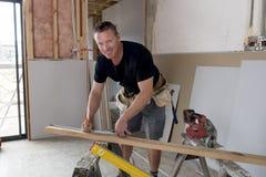 愉快的可爱和确信的建设者木匠或建造者人运作的和测量的木头在浓缩工业建筑的工作 库存图片