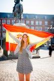 年轻愉快的可爱的交换学生女孩获得乐趣在参观马德里市的镇里显示西班牙旗子 免版税图库摄影