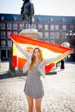 年轻愉快的可爱的交换学生女孩获得乐趣在参观马德里市的镇里显示西班牙旗子 免版税库存图片