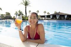 愉快的可爱的在水池的lation妇女饮用的鸡尾酒 免版税图库摄影