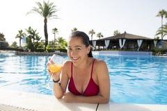 愉快的可爱的在水池的lation妇女饮用的鸡尾酒 免版税库存图片
