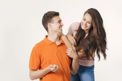 愉快的可爱的夫妇互相微笑和谈话关于某事 工作室被射击在空白背景 免版税库存照片