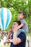 愉快的可爱的女儿坐父亲肩膀戏剧并且获得乐趣在公园在夏天晴天愉快的孩子本质上 库存照片