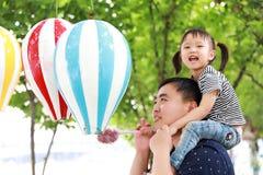 愉快的可爱的女儿坐父亲肩膀戏剧并且获得乐趣在公园在夏天晴天愉快的孩子本质上 免版税库存图片