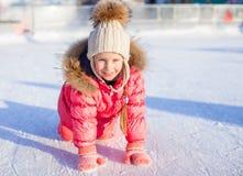 愉快的可爱的女孩坐与冰鞋的冰 图库摄影