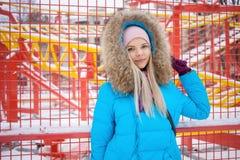 年轻愉快的可爱的妇女多云室外冬天画象摆在冬天城市公园的明亮的深蓝外套的反对明亮红色和 库存图片