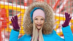 年轻愉快的可爱的妇女多云室外冬天画象摆在冬天城市公园的明亮的深蓝外套的反对明亮红色和 免版税库存图片