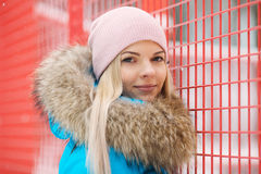 年轻愉快的可爱的妇女多云室外冬天画象摆在冬天城市公园的明亮的深蓝外套的反对明亮红色和 库存照片