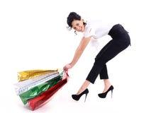 愉快的可爱的妇女扯拽购物袋。 免版税图库摄影