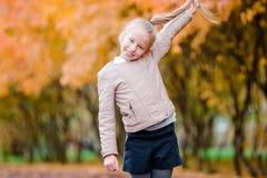 愉快的可爱的小女孩获得乐趣户外美好的秋天天 免版税库存图片