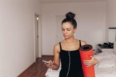 愉快的可爱的少妇在手红色瑜伽或健身席子举行在家解决以后在客厅 健康 免版税库存照片